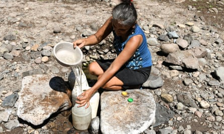 Maria Gutierrez, collects water from a hole in the sand, at the 'El Salto' stream, whose bed is almost completely dry, in San Francisco de Coray municipality, 100km south of Tegucigalpa, a rural community under emergency due to severe drought, on 10 September.