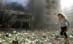 A woman runs past a destoyed building in Beirut, Lebanon, after it was attacked by Israel.