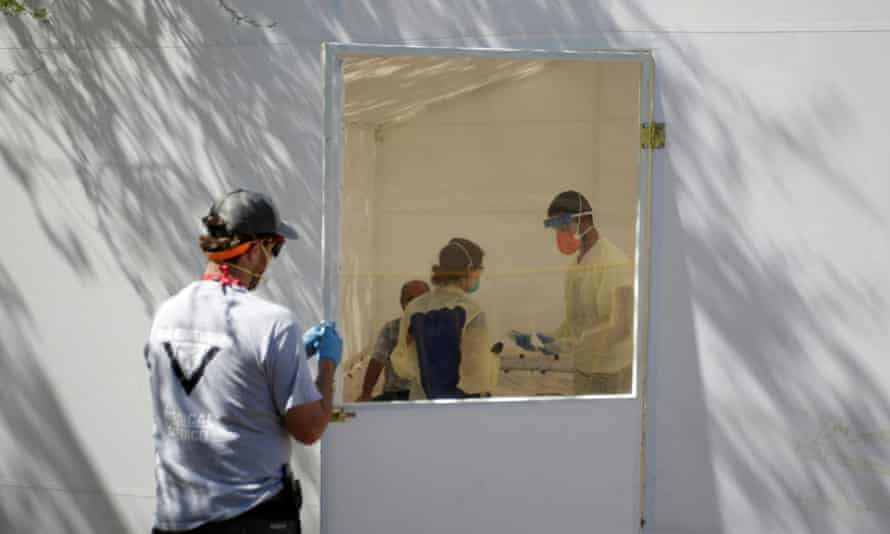 Medical staff take samples from a patient suspected of having coronavirus in a hospital at a migrant encampment in Matamoros.