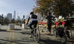 People pass by the makeshift memorial for victims of Tuesday's terrorist attack along a bike path in lower Manhattan on Friday with the World Trade Center in the background.
