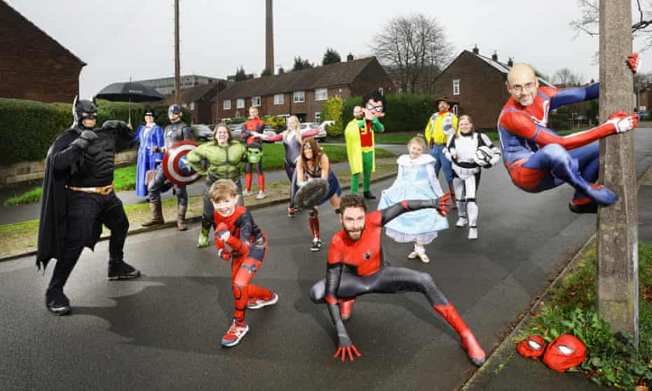Stockport Spider-Men Jason Baird (front) and Andrew Baldock (up lamp-post), photographed with other superhero runners they inspired
