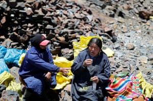 Eva Chura and another pallaquera smoke and drink anise while chewing coca leaves, as part of a ritual for searching for gold performed before a shift
