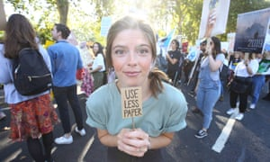 A young climate striker with a tiny placard reading 'Use less paper'