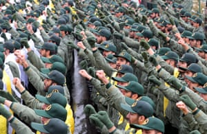 Members of the Revolutionary Guards raise their fists while shouting slogans