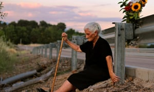 María Martín sits by the road which covers the mass grave containing her mother's remains.