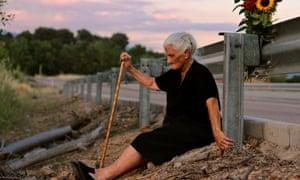 María Martín se sienta en el camino que cubre la fosa común que contiene los restos de su madre
