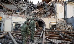 Croatian Soldiers walk on wreckage next to damaged buildings in Petrinja, Croatia.
