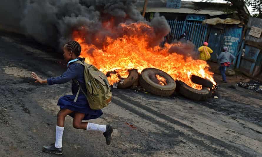 A schoolgirl runs past a burning barricade in Kibera slum, Nairobi.