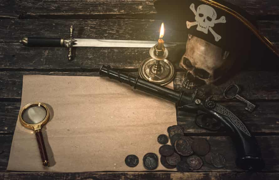 Pirate treasure map with pirate captain hat, coins, magnifying glass, human skull, musket, dagger and burning candle