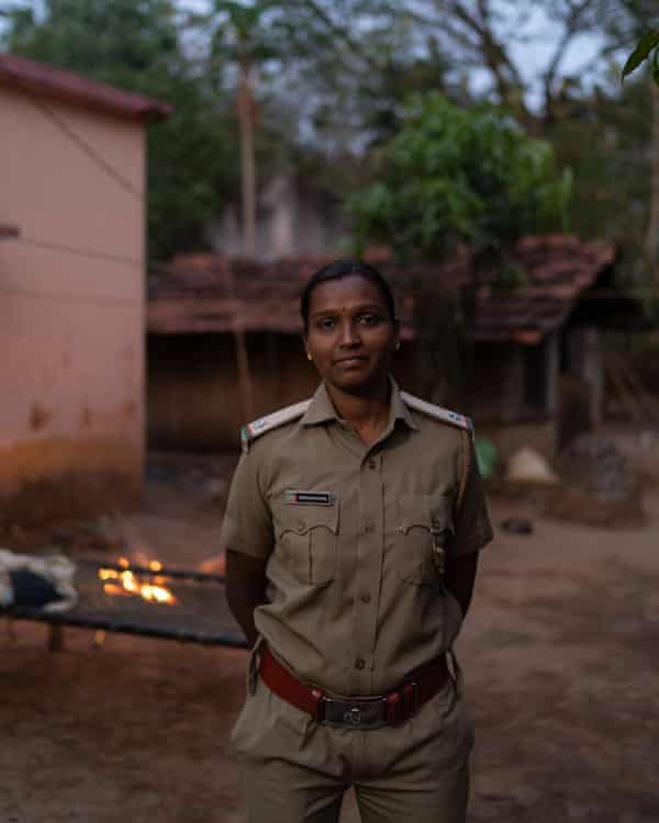 Snehalata Dhal standing in front of small fire.