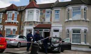 Police officers work leave a residential property in Ilford, east of London