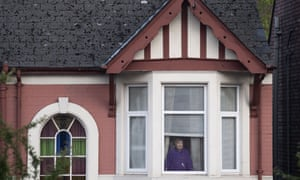 A woman looks out from an upstairs window in Newport, Wales.
