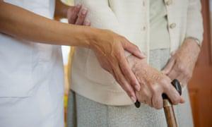 A caretaker helps an older woman walk