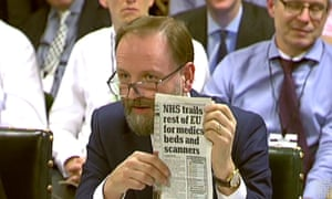 Simon Stevens holds up a copy of the Daily Mail at a combative meeting of the public accounts committee about the crisis in the health service.