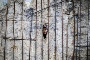 A tourist from Greece looks through the hole in remains of the Berlin Wall after commemorations celebrating the 30th anniversary of the fall of the Berlin Wall at Bernauer Strasse.