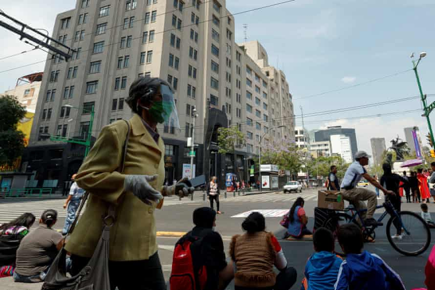 People wear masks as they walk the streets of Mexico City.