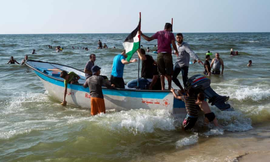A small pleasure boat on a Gaza city beach takes bathers on a joy ride out to sea beyond the 200m limit contaminated by sewage.