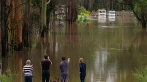 People looking at trucks stuck on a flooded road in Taree, NSW
