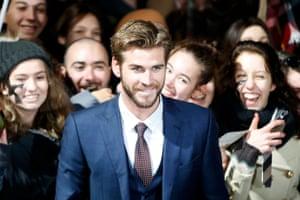 A fan photobombs Liam Hemsworth's photocall