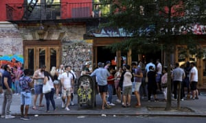 People drink outside a bar during the reopening phase following the coronavirus lockdown in the East Village neighborhood of New York City on 13 June.