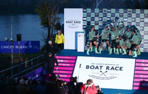 The Cambridge University Men's Boat Club Blue crew celebrate with the trophy after victory over Oxford.