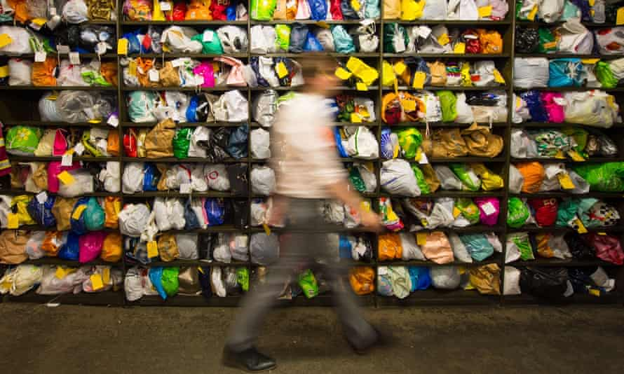 A member of staff walks past bags of clothing