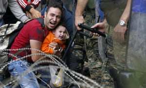 A migrant man holds a boy as they are stuck between Macedonian riot police and migrants near the border train station of Idomeni, northern Greece.