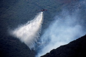 A helicopter makes a water drop during the Bobcat fire.