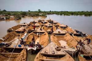A convoy of boats used to carry sand extracted from the riverbed sails along the Niger River between Kangaba, in Mali's south-western Koulikoro region, and Bamako
