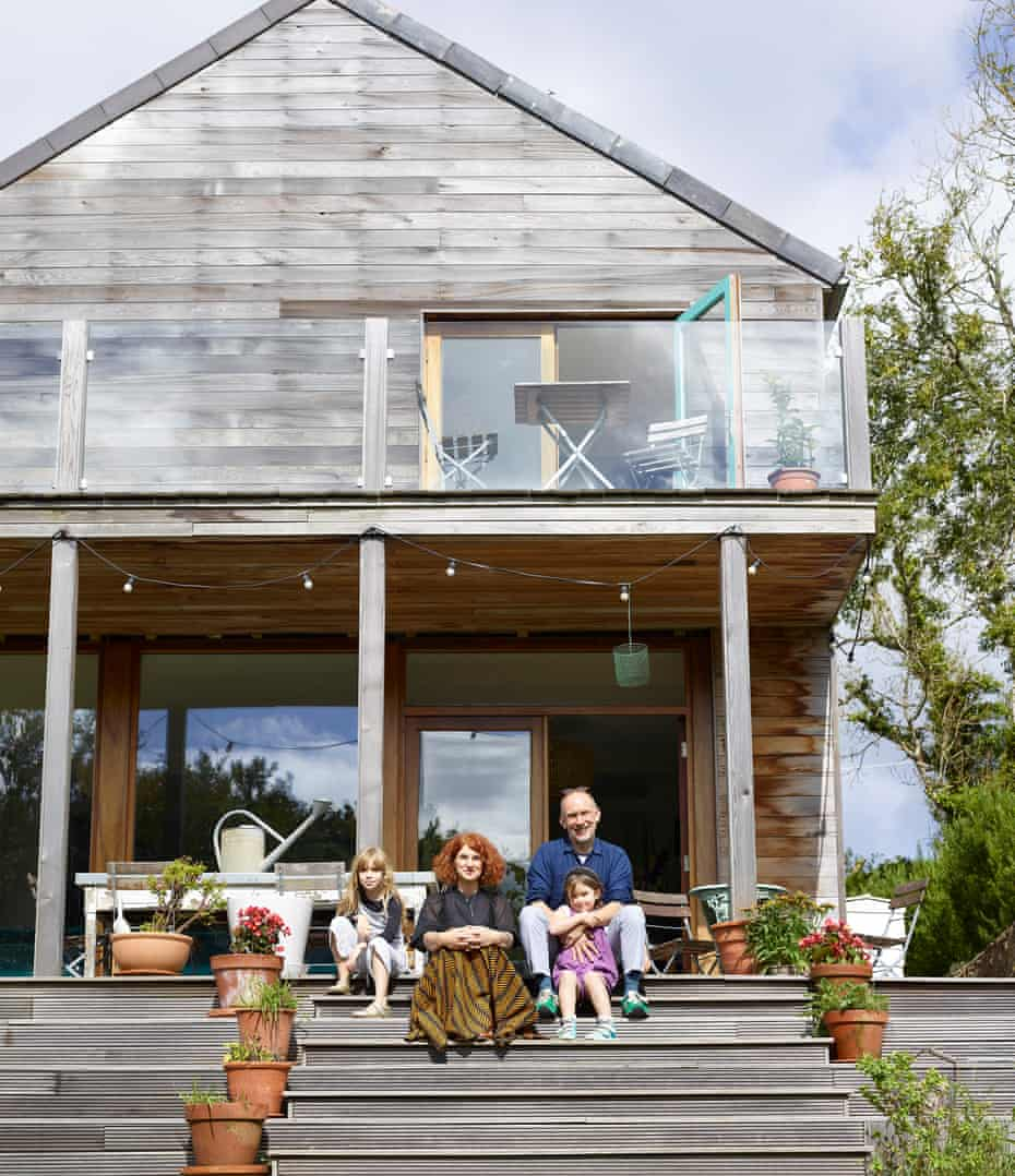 The Anglesey house seen from the outside with Mairead Turner and family sitting on the wooden steps, the house and balcony behind them