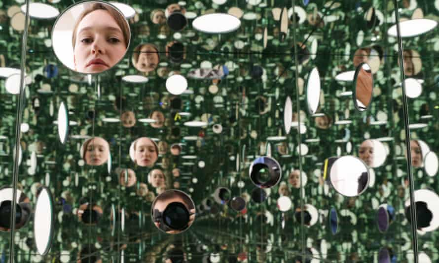 An employee poses in front of The Passing Winter 2005 by Japanese artist Yayoi Kusama