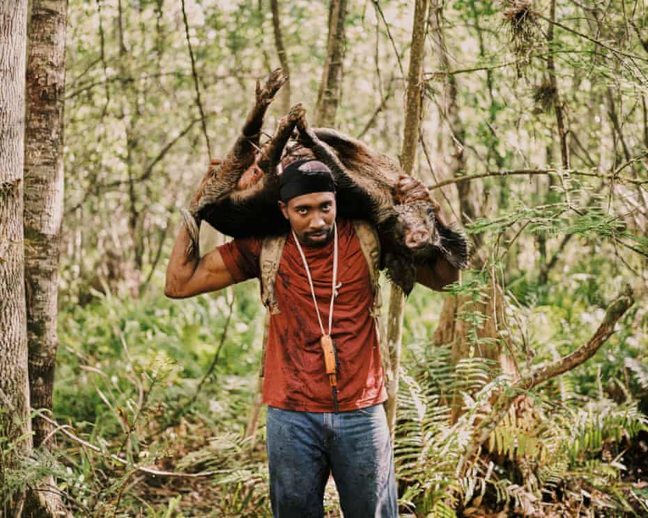 Pompi Rodriguez carries a captured hog out of the marsh.