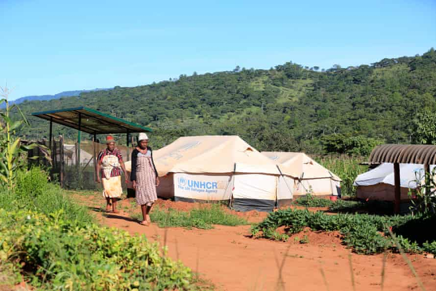 Women in Ngangu, Chimanimani, walk past tent shelters