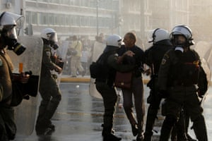 A protester scuffles with riot police officers during a protest against Covid vaccinations outside the Greek parliament building in Athens.