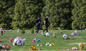 A couple is seen among the graves at Greenwood Cemetery in Brooklyn, New York City, 7 May 2020.