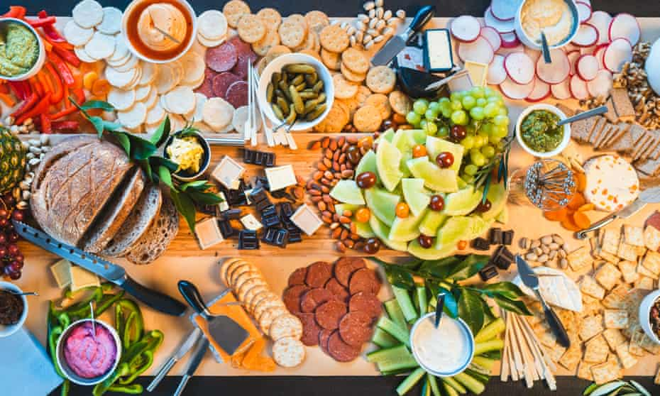 An Australian cheese platter that features many elements of global cuisine including hummus, pesto, guacamole and tzatziki.