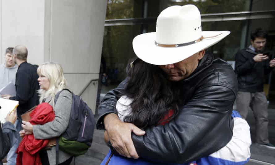 Defendant Shawna Cox speaks at left as supporters hug outside federal court in Portland, Oregon, on Thursday.