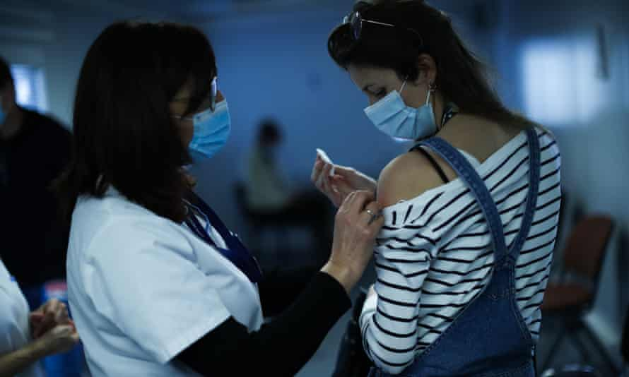 A nurse administers a Covid-19 vaccine to a healthcare worker in Liege, Belgium, 27 January 2021.