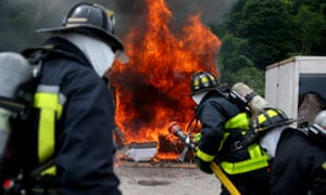Boston firefighters observe a pod without a sprinkler as furniture and other items burn during a demonstration.