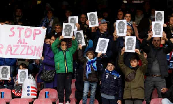 Fans hold up photos of Koulibaly and an anti-racism banner