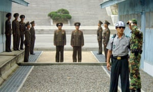 North Korean soldiers stand guard as South Korean soldiers chat in the DMZ.