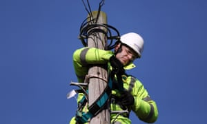 A trainee engineer from Openreach checks his safety harness at the top of a telegraph pole.