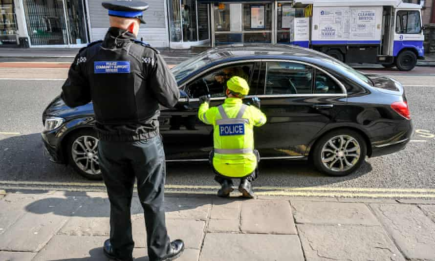 Police stop a motorist in Bristol on Friday in a random check on essential travel.