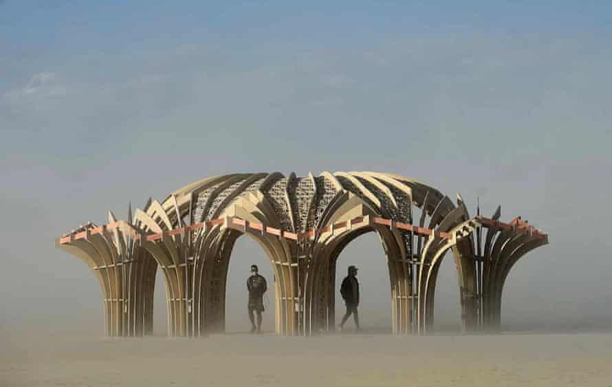 Burners stand inside an art sculpture during a dust storm.