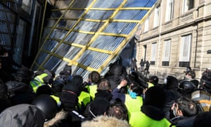 Gilets jaunes protesters remove a barrier protecting a shop window on the Champs Élysées