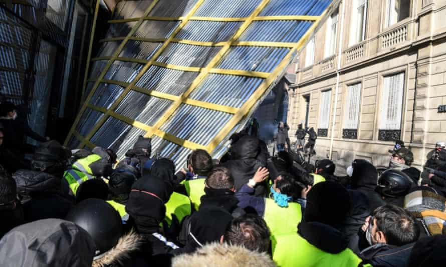 Gilets jaunes protesters remove a barrier protecting a shop window on the Champs Élysées