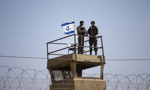 Israeli soldiers guard a watchtower on the Israel-Gaza border