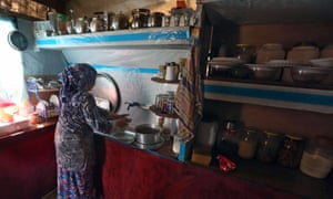 Syrian refugee Um Ahmed washes dishes in a tent at a camp in the Bekaa valley area of Lebanon.