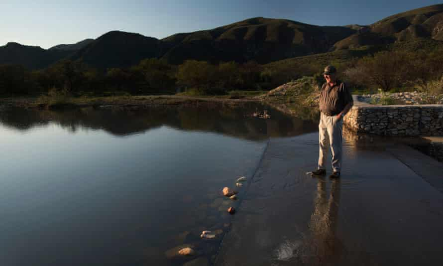 Farmer Pieter Kruger stands on a weir on his farm
