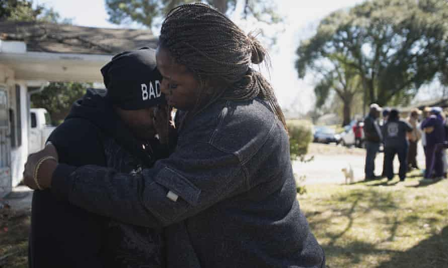Kimberly Gunn, sister of Greg Gunn, is embraced by family friend Pam Blocton while mourning.
